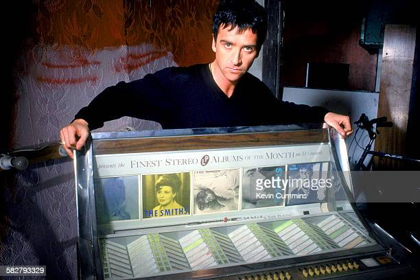 English guitarist and songwriter Johnny Marr leaning on a jukebox featuring singles by his former group The Smiths circa 1990