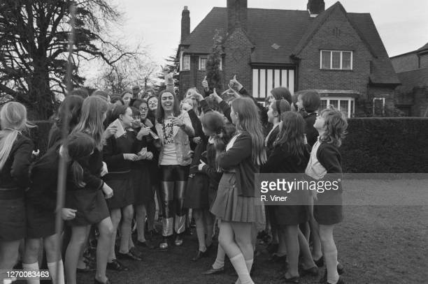 English guitarist Dave Hill of the band Slade surrounded by teenage fans from nearby Saint Martin's School outside his new home in Solihull...
