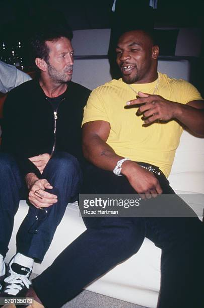 English guitarist Eric Clapton and American boxer Mike Tyson attending a party for Giorgio Armani at the Park Avenue Armory New York City USA circa...