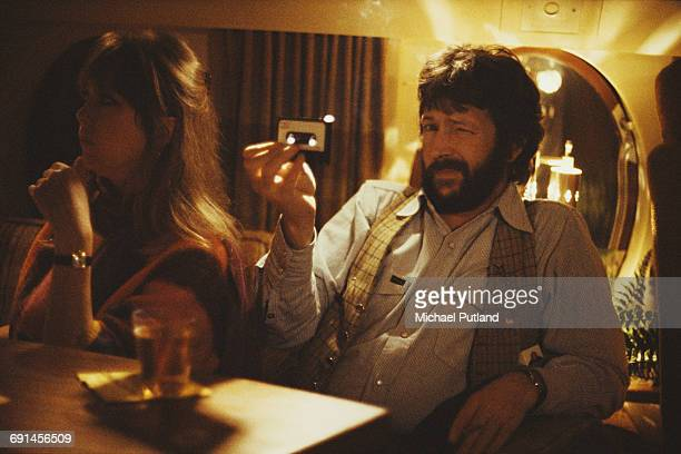 English guitarist Eric Clapton holding an audio cassette tape on board a private jet, USA, 1978. With him is his girlfriemd, model Pattie Boyd.