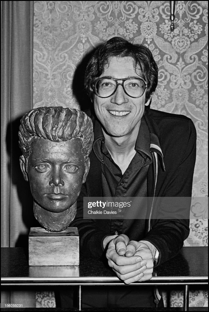 English guitarist Hank Marvin poses next to a wooden bust of Cliff Richard at his manager's office, London, 1977.