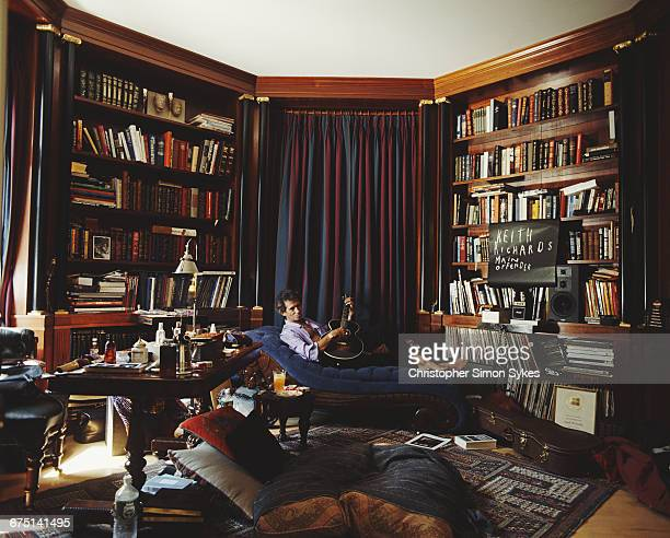 English guitarist Keith Richards of the Rolling Stones playing a guitar on a chaise longue in his library circa 1995