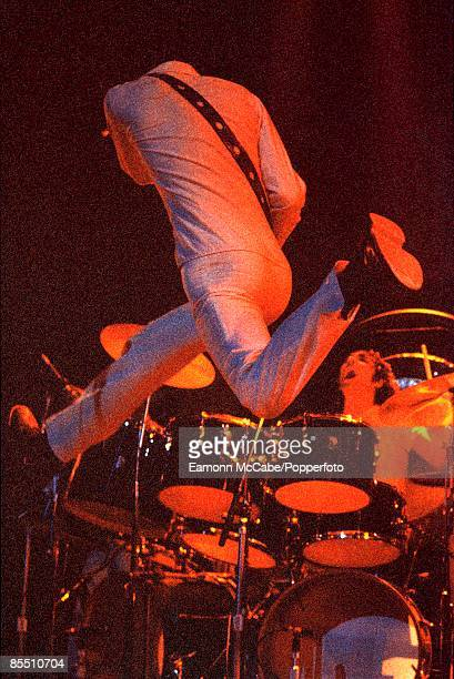 English guitarist Pete Townshend leaps in the air in front of drummer Keith Moon during a concert by The Who circa 1973