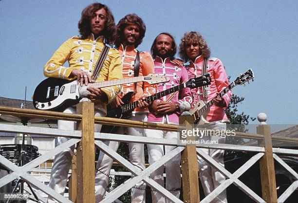 English guitarist Peter Frampton with pop vocal trio the Bee Gees in costume on the set of the film 'Sgt Pepper's Lonely Hearts Club Band' directed...