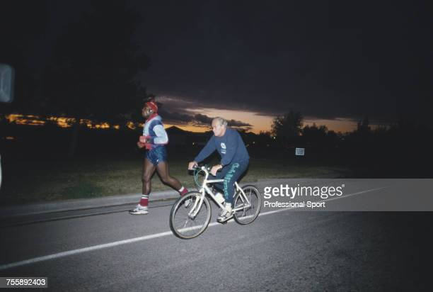 English heavyweight boxer Frank Bruno pictured on a training run with his trainer George Francis riding a bicycle beside him during a training...