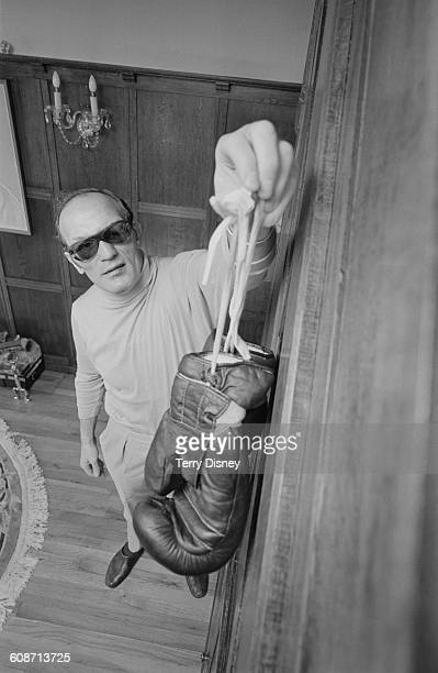 English heavyweight boxer Henry Cooper hangs up his gloves to symbolise his retirement from boxing UK 17th March 1971 The day before he had lost his...