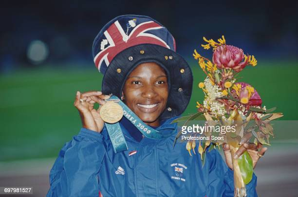 English heptathlete Denise Lewis pictured holding up her gold medal after finishing in first place for Great Britain in the Women's heptathlon event...