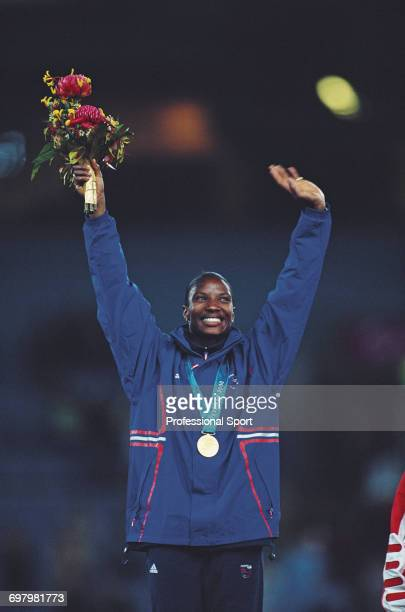 English heptathlete Denise Lewis pictured waving in celebration on the medal podium after finishing in first place to win the gold medal for Great...