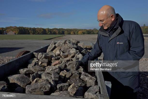 English historian and Holocaust specialist David Cesarani standing by a quarry cart filled with rocks at the site of the former Buchenwald German...