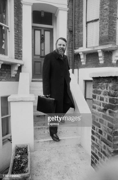 English humanitarian and author Terry Waite holding a briefcase on the steps of a Victorian house, UK, 31st December 1984.