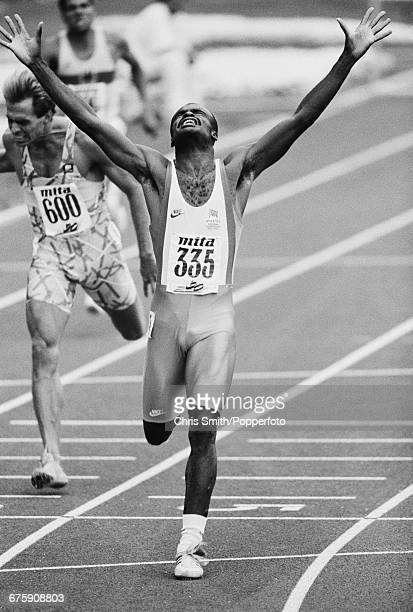 English hurdler Kriss Akabusi competing for Great Britain throws his arms in the air in celebration after crossing the finish line in first place to...