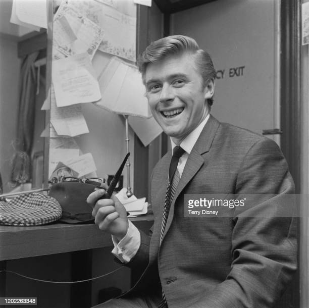 English impressionist and comedian Mike Yarwood holds a pipe in a dressing room backstage at a theatre on 14th June 1965 Mike Yarwood uses the pipe...