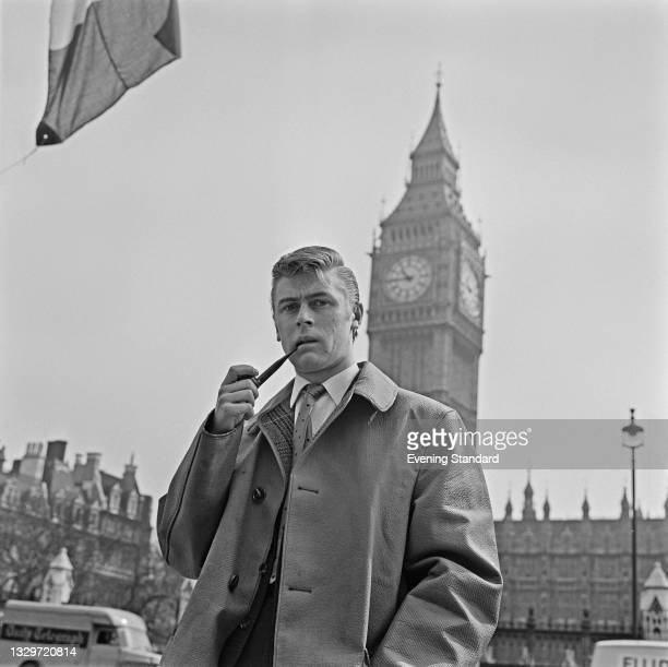 English impressionist and comedian Mike Yarwood in front of the Palace of Westminster in London, UK, 14th May 1965. He is smoking a pipe in imitation...