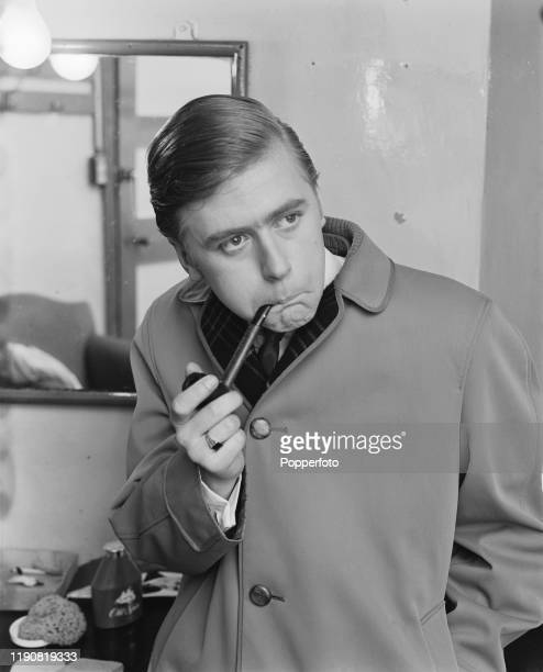 English impressionist and comedian Mike Yarwood performs an impression of pipe smoking prime minister Harold Wilson in a backstage dressing room in...