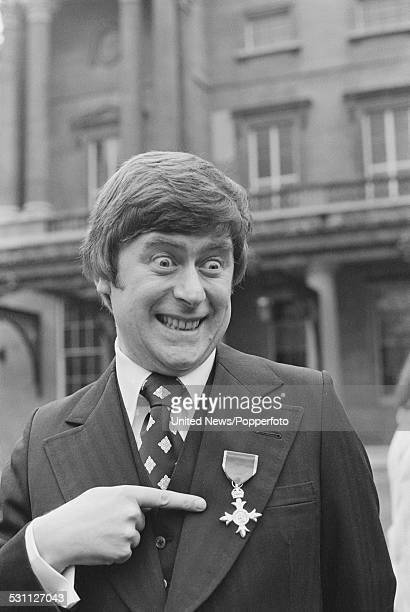 English impressionist Mike Yarwood pictured pointing to his OBE at an investiture ceremony at Buckingham Palace in London on 8th December 1976