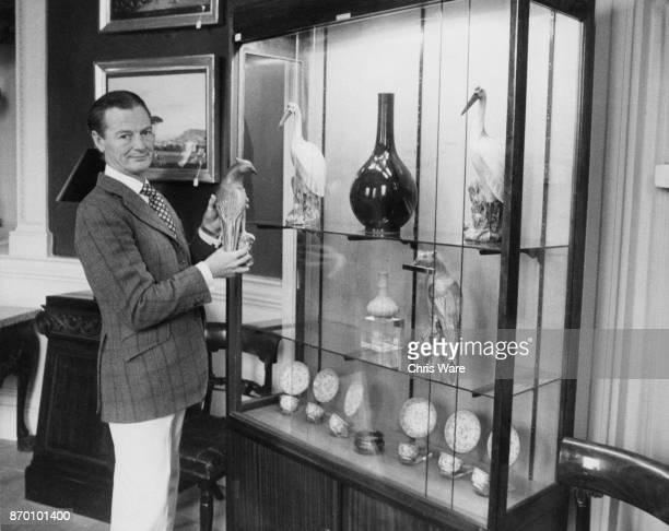 English interior designer David Nightingale Hicks with a pair of enamelled pheasants from the Chien Lung period at his home Britwell House in...