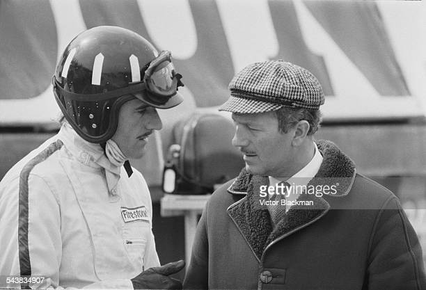 English inventor, engineer, and founder of Lotus Cars Colin Chapman with British racing driver Graham Hill taking a break from practice sessions at...