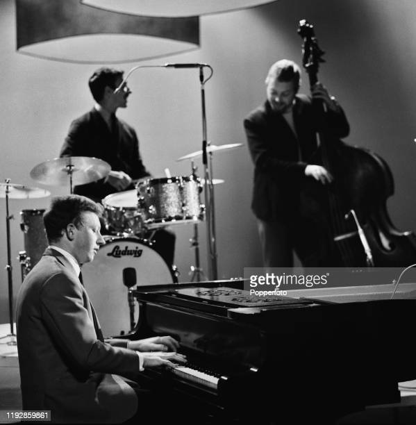 English jazz pianist Roy Budd performs with bassist Dave Holland and drummer Chris Karan on 'The Des O'Connor Show' for Associated Television in June...