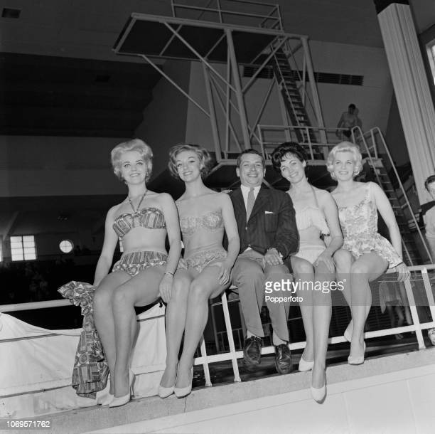 English jazz singer George Melly pictured in centre with four young female models in swimsuits beside the diving boards at the Derby Baths during the...