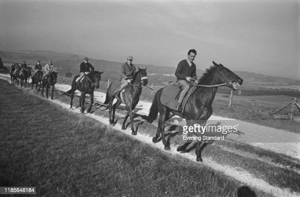 English jockey and trainer Josh Gifford leads a line of racehorses for an exercise run near his stables on the South Downs in West Sussex England on...