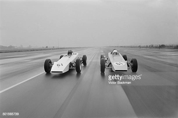 English jockey Lester Piggott receives driving tips from racing driver Graham Hill in a Lotus Ford at the Lotus test circuit at Hethel Airfield...