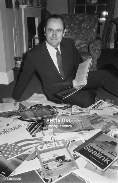 English journalist and biographer Tom Pocock , Travel Editor of the Evening Standard, with a pile of travel brochures, UK, 3rd January 1974.