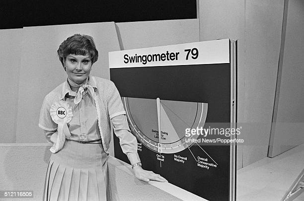 English journalist and newsreader Angela Rippon posed beside the swingometer in a BBC television studio set in preparation for an upcoming election...