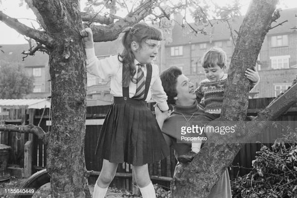 English journalist and writer Claire Rayner pictured with her daughter Amanda and son Adam in the back garden of their house in November 1965