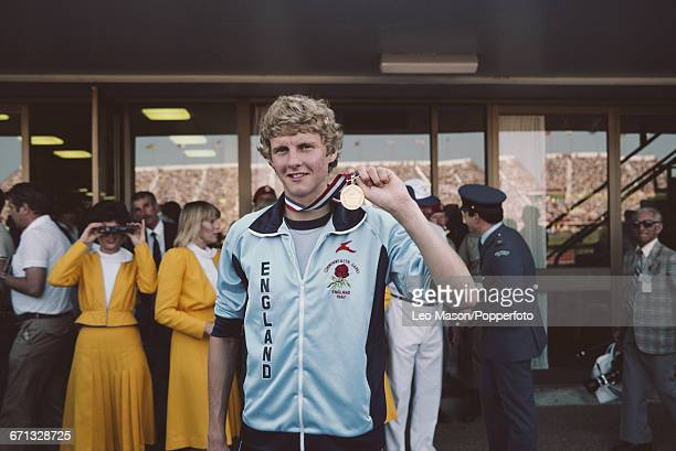 English middle distance runner Steve Cram holds up the gold medal he was awarded after finishing in first place in the 1500 metres event at the 1982...