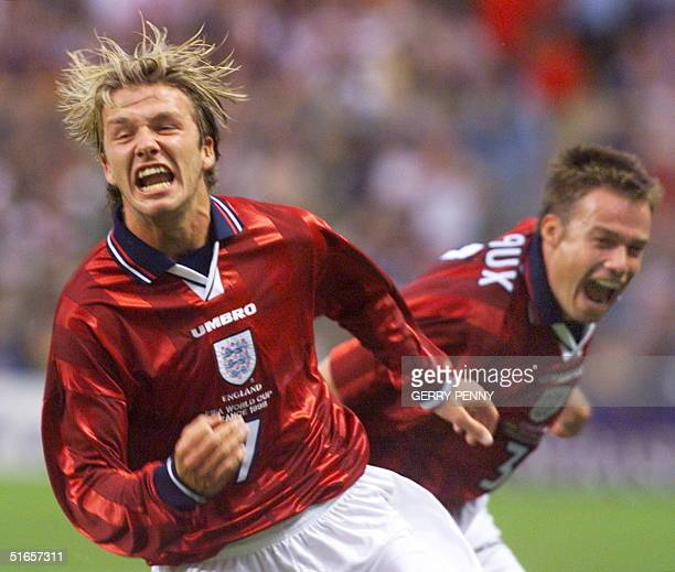 English midfielder David Beckham jubilates after he scored the second goal of his team next to teammate Graeme Le Saux 26 June at the Felix Bollaert...