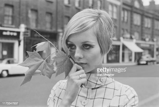 English model actress and singer Twiggy holds a maple leaf while standing in the middle of King's Road in Chelsea London UK 13th June 1966