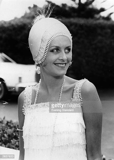 English model, actress and singer Twiggy wearing a 1920s-style beaded cap and dress.