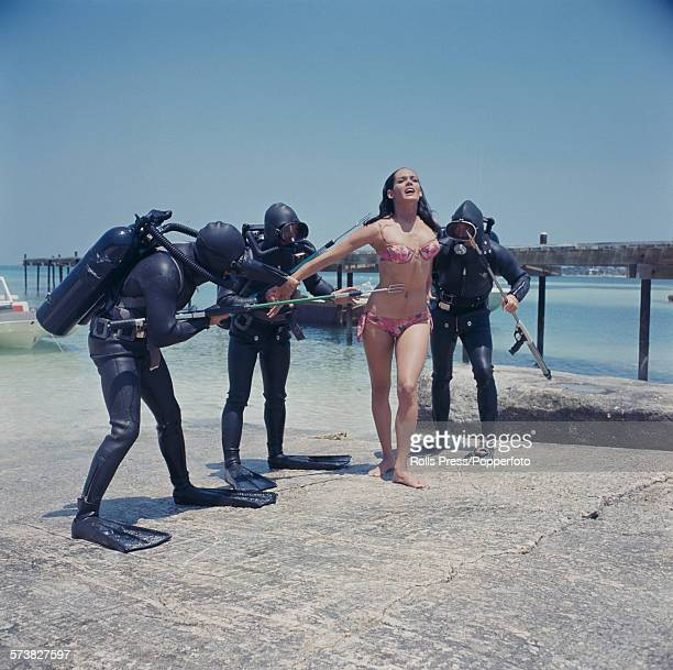 English model and actress Martine Beswick pictured in character as Paula Caplan wearing a pink floral bikini being attacked by frogmen armed with...