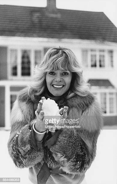 English model and actress Mary Millington who appears in the adult film 'Come Play With Me' pictured wearing a fur coat and holding a snowball in...