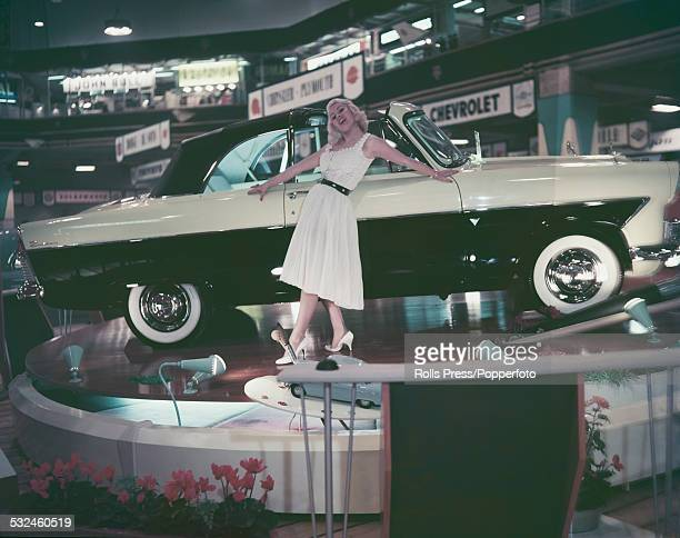 English model and actress Rita Royce pictured posing beside a new Ford Zodiac Mark II model at the Earls Court motor show in London in 1958