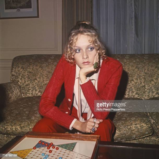 English model and actress Twiggy pictured wearing a red cardigan and trousers as she sits on a sofa with a game of Chinese checkers in front of her...