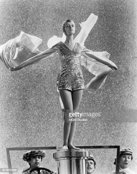 English model and actress Twiggy poses on the bonnet of a car in imitation of the Rolls Royce mascot 'Spirit of Ecstasy' in a scene from the fim...