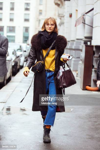 English model Fran Summers holds an iPhone and wears a brown leather coat with a fur collar a black scarf yellow sweater blue jeans a black leather...