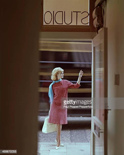English model Jean Shrimpton poses in the doorway of a studio wearing a pink suede suit with a cardigan jacket 1962