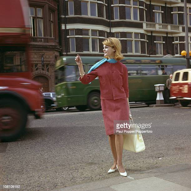 English model Jean Shrimpton wearing a pink suede suit with a blue scarf and white handbag London 1962