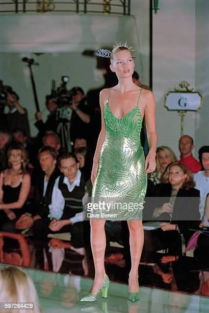 English model Kate Moss wearing a green cocktail dress with matching heels on the catwalk at the Gianni Versace Haute Couture Summer 1996 launch at...