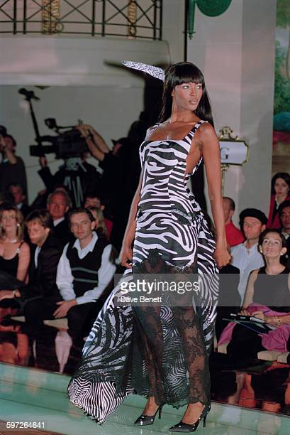 English model Naomi Campbell wearing a full length black lace and zebrastriped dress with a matching feather in her hair on the catwalk at the Gianni...