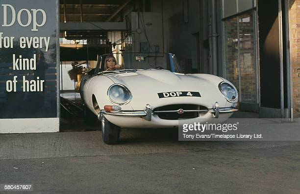 English model Pattie Boyd filming a commercial for Dop Pearlized Shampoo by L'Oreal, UK, 1966. Here she exits a car wash in a Jaguar E-type roadster...