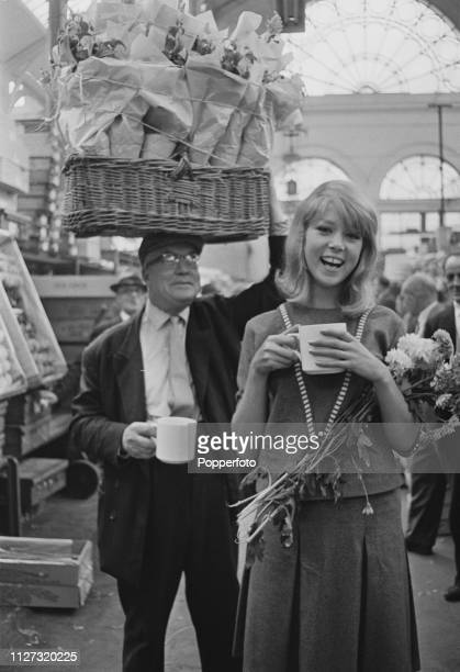 English model Pattie Boyd pictured buying flowers during a visit to Covent Garden market in Covent Garden, London in September 1963.