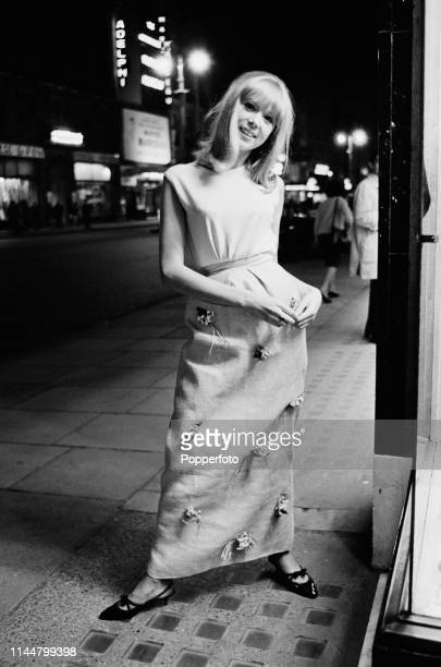 English model Pattie Boyd pictured wearing a full length skirt and sleeveless top as she stands on the Strand in London in August 1964