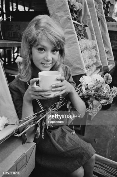 English model Pattie Boyd pictured with a mug of tea during a visit to Covent Garden market in Covent Garden, London in September 1963.
