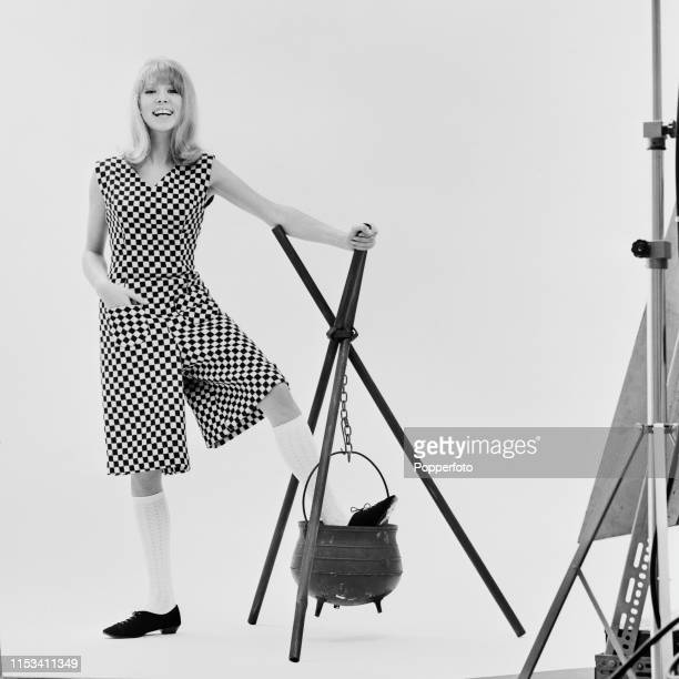 English model Pattie Boyd wears black and white monochrome knee length all-in-one culottes or culottes jumpsuit during a halloween themed modelling...