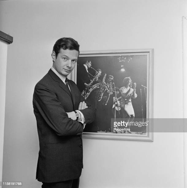 English music entrepreneur Brian Epstein , manager of The Beatles, pictured standing beside a photograph of Cilla Black, one of his artists, at home...