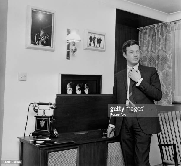 English music entrepreneur Brian Epstein , manager of The Beatles, pictured playing a record on a music centre at home in London in April 1965....