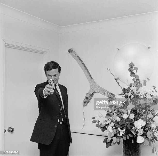 English music entrepreneur Brian Epstein , manager of The Beatles, pictured pointing a replica revolver at the camera at home in London in April 1965.